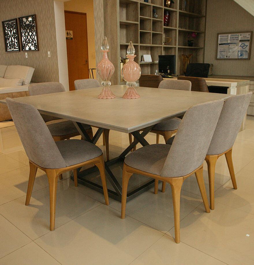 Mesa de jantar em cores sóbrias, cadeiras estofadas da mesma cor do tampo de vidro e pés em madeira clara que destacam o móvel.