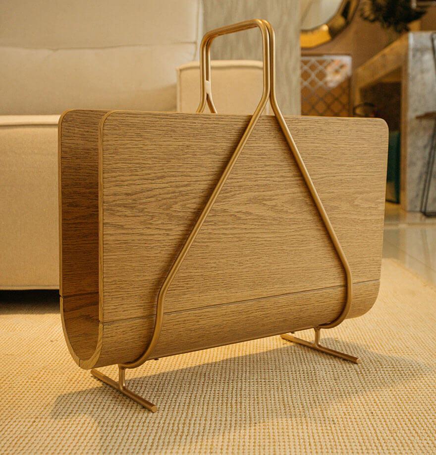 Revisteiro de madeira com suporte em dourado.